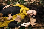 happy  beautiful woman  lie in grass and autumn leaves wearing dark green dress and long yellow wool scarf hold in hand leaf