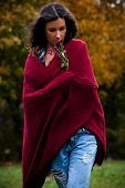 young woman with long curly hair wrapped in  red wool scarf outdoor shot autumn day in park
