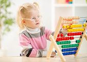 Funny kid in eyeglases counting with abacus