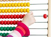 Kid's hand with colorful abacus on white background