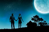Silhouettes of young romantic couple standing under the moon light