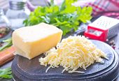 pic of grating  - grated cheese on the wooden board and on a table - JPG