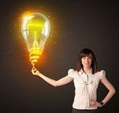Businesswoman holding a shining, idea bulb