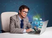 Attractive young man sitting at desk and watching his photo gallery on laptop