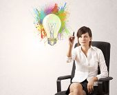 Young lady drawing a colorful light bulb with colorful splashes on white background