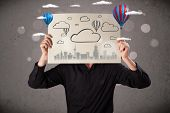 Businessman holding a cardboard in front of his head with cityscape and ballons drawing