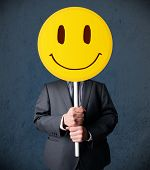stock photo of emoticon  - Businessman holding a yellow smiley face emoticon in front of his head - JPG