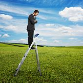 displeased businessman standing on the pair of steps and looking down. photo over green field and blue sky