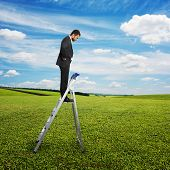 serious businessman standing on the pair of steps and looking down. photo over green field and blue sky