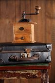 Nostalgic coffee grinder on old stool and vintage suitcase  with textured wood background