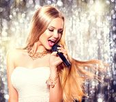 picture of singing  - Beauty model girl singer with a microphone singing and dancing over holiday glowing background - JPG