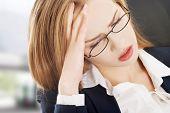 Sad, worried caucasian business woman sitting