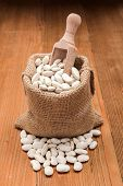 picture of phaseolus  - Dry loose haricot beans in burlap sack on wooden board background - JPG