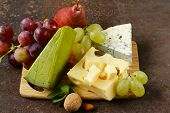 cheeseboard with different types of cheese and grapes
