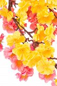 Artificial branch with yellow and pink flowers.