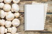 Mushrooms With Blank Cooking Book Or Recipe Sheet On Wood Background