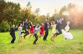 Newlyweds with guest jumping in park