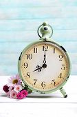 Beautiful flowers with clock on table on light blue background