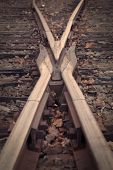 Close up of crossover railroad train tracks. Vintage filter / effect and vignette applied.