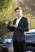 Man with car key outdoors