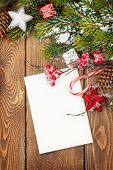 Christmas greeting card or photo frame over wooden table with snow fir tree. View from above