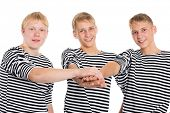 Young men in striped shirts in friendship joined his hands. Two of the boys twin brothers.