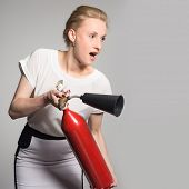 An excited young blonde woman with a fire extinguisher