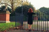 pic of hackney  - A young woman is leaning on a gate in a park in the autumn