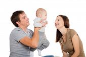Happy mother and father playing with his young son. Child seven months.