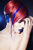 Young person with blue eye shadows blue ears and pink hair with blue strand on it