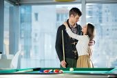 Beautiful couple standing next to the pool table, selective focus