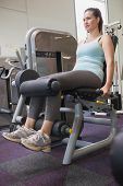 Fit brunette using weights machine for legs at the gym