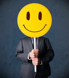 picture of emoticon  - Businessman holding a yellow smiley face emoticon in front of his head - JPG