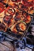 stock photo of charcoal  - grilling spiced chicken in grid on charcoal bbq with tomatoes and vegetables - JPG