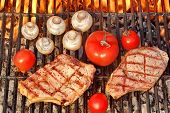 image of ribs  - Two Rib Steaks Tomato and Mushrooms Roasted Over Flaming BBQ Grill - JPG