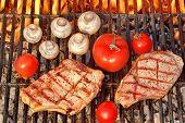 foto of rib eye steak  - Two Rib Steaks Tomato and Mushrooms Roasted Over Flaming BBQ Grill - JPG