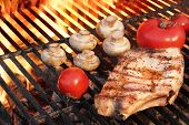picture of rib eye steak  - Rib Steak Tomato and Mushrooms Roasted Over Flaming BBQ Grill - JPG