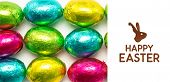 stock photo of easter candy  - happy easter graphic against colourful foil wrapped easter eggs overhead shot - JPG