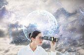 image of binoculars  - Business woman looking through binoculars against global technology background in blue - JPG