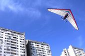 stock photo of hang-gliding  - The motorized hang glider flying over residential buildings in the city - JPG