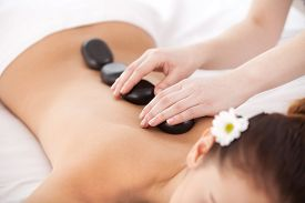 picture of stone-therapy  - Top view of young woman lying on front while massage therapist massaging her back with spa stones - JPG