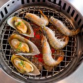 stock photo of roster  - Closeup grilled seafood prawns and squids on fire background - JPG