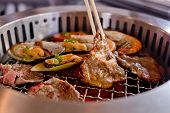 stock photo of braai  - Mixed Roasted Meat and Seafood and Chopsticks on the BBQ Grill on roast - JPG