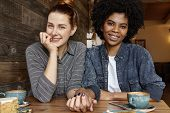 Interracial Gay Couple Relaxing Indoors. Cute Caucasian Woman With Hair Bun Holding Hand Of Her Styl poster