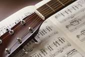 Guitar close up on sheet music background