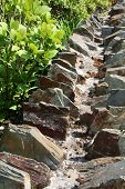 image of fieldstone-wall  - Old stone wall showing weathering by the sea and sun - JPG