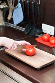 Female Hands In Kitchen Interior Cuts A Tomato On A Cutting Board