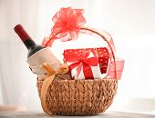 Wine bottle with gift boxes in wicker basket on light background poster