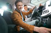 Man sitting inside vehicle in car dealership poster
