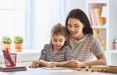 Happy family. Mother and daughter are learning to write. Adult woman teaches child the alphabet. poster